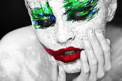 Bright portrait of girl with an unusual make-up. Horror. Halloween. Horror portrait of a girl with an creative make-up in joker style Royalty Free Stock Photo
