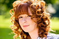 Bright portrait of red-haired young woman outdoors. Close-up bright portrait of red-haired lovely young woman outdoors Stock Images