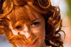 Bright portrait of red-haired young woman outdoors. Close-up bright portrait of red-haired lovely young woman outdoors Royalty Free Stock Image