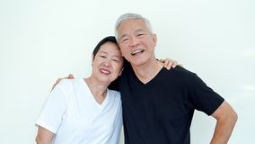 Bright, positve and happy Asian elderly married couple on white Stock Photography
