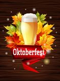 A bright poster on the Oktoberfest beer festival. Autumn maple leaves on a wooden background, the effect of the sun glow. Vector illustration Stock Photos