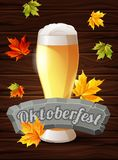 Bright poster Oktoberfest, beer, holiday. Autumn maple leaves on the wooden background. The inscription on the stone. Tablet. Vector illustration Royalty Free Stock Images