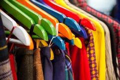 Racks with hanging clothes. Stock Photos