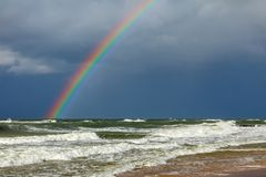 Bright rainbow on the background of storm clouds over the raging sea.  royalty free stock photos