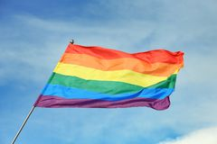 Bright rainbow gay flag fluttering against blue sky. LGBT community stock image
