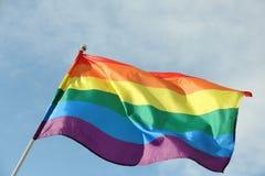 Bright rainbow gay flag fluttering against blue sky. LGBT community royalty free stock photo