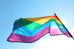 Bright rainbow gay flag fluttering against blue sky. LGBT community. Bright rainbow gay flag fluttering against blue sky, bottom view. LGBT community royalty free stock photo