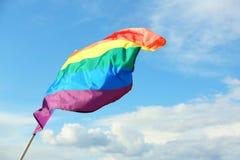 Bright rainbow gay flag fluttering against blue sky. LGBT community. Bright rainbow gay flag fluttering against blue sky, space for text. LGBT community royalty free stock photos