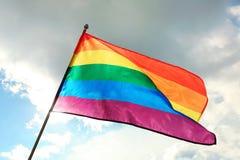 Bright rainbow gay flag fluttering . LGBT community. Bright rainbow gay flag fluttering against blue sky. LGBT community royalty free stock image