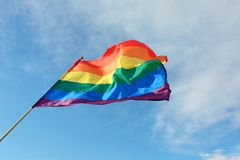 Bright rainbow gay flag fluttering. LGBT community. Bright rainbow gay flag fluttering against blue sky. LGBT community royalty free stock images