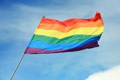 Bright rainbow gay flag fluttering . LGBT community. Bright rainbow gay flag fluttering against blue sky. LGBT community stock photography