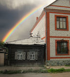 Bright rainbow of hope for new habitation. Rainbow uniting a small house in old style with the new modern house