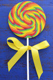 Bright rainbow lollipop candy on dark blue wood table. Stock Photo