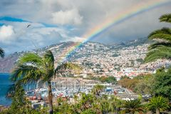 Bright rainbow over the harbor town from left to right. Bright rainbow rising to the right. Palms, trees and a yacht club in the foreground, sunny town on the stock images