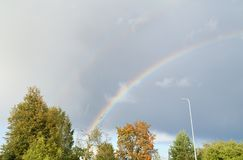 Bright rainbow over trees at small city. royalty free stock photos