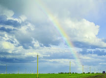 Bright rainbow in the stormy sky over the meadow Stock Photos