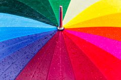Bright rainbow umbrella covered with rain drops texture royalty free stock images