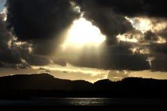 Bright rays of the sun shine trough dark clouds. Bright rays on the sun shine through dark clouds over lake. Dramatic sky Royalty Free Stock Photo