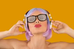 Trendy glamorous woman in headphones. Bright rebellious girl in wig and glam sunglasses listening to music confidently Royalty Free Stock Photo