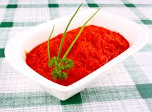 Bright red ajvar in white bowl with chives and parsley Stock Photo