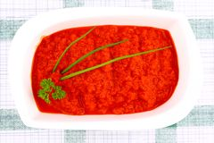 Bright red ajvar in white bowl with parsley, spring onion Stock Photo