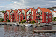 Bright red apartment buildings with Yachts moored in front Royalty Free Stock Photo