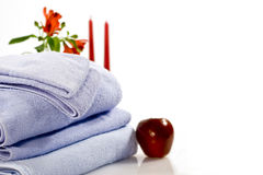 Bright red apple, red flowers and towels Royalty Free Stock Photo