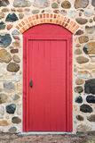 Bright Red Arched Door in a Stone Wall Royalty Free Stock Image