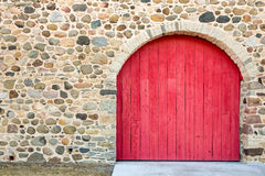Bright Red Arched Door in a Stone Wall Stock Images
