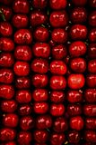 Bright red background from neatly folded juicy sweet cherries. stock photos