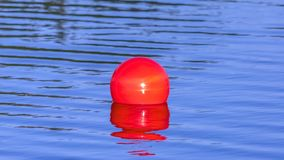 Bright red ball floating on the calm Oquirrh Lake. A bright red ball floating on Oquirrh Lake in Daybreak, Utah. The ball is reflected on the glassy water of stock images