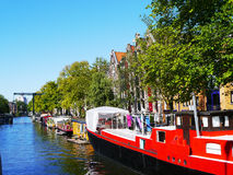 Bright red barge on Amsterdam canal. A bright red barge contrasts sharply against the blue waters of the canal and the bright sky above stock image