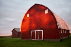 Bright red barn with grey overcast skies overhead stock photography