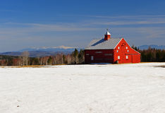 Bright red barn and snow covered field Royalty Free Stock Photos