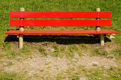 Bright red bench on a green meadow Royalty Free Stock Photos