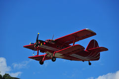 Bright Red Bi-plane. Red biplane against deep blue sky. This model is an Antonov AN-2 Royalty Free Stock Photos