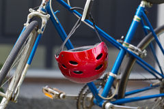 Bright red bicycle helmet hanging from handle bars. Closeup image of used red bicycle helmet with home in background Stock Photography