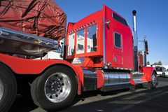 Bright red big rig classic American semi truck with flat bed semi trailer carry commercial cargo covered and fixed by slings stan. Bright red big rig classic royalty free stock image