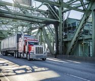 Free Bright Red Big Rig Classic Semi Truck With Chrome Accessories Transporting Cargo In Covered Van Semi Trailer Driving On The Truss Royalty Free Stock Photo - 173311195