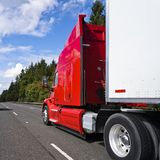 Bright red big rig long haul semi truck with high cabin transporting cargo in semi trailer driving on multiline road. Bright red bonnet American modern long haul royalty free stock photos