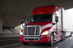 Bright red big rig semi truck with dry van trailer driving on hi. Bright red big rig modern semi truck fleet with shiny chrome grille and dry van trailer driving Stock Image