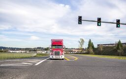 Free Bright Red Big Rig Powerful Semi Truck With Grille Guard Driving On The Road Standing On Crossroad Intersection Waiting For Green Stock Photo - 177079490