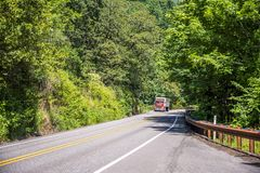 Bright red big rig semi truck transporting commercial cargo moving on the green forest winding road. Big rig red powerful American bonnet long haul semi truck royalty free stock photo