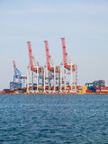 Bright red and blue cranes and colorful maritime containers stan Stock Photo