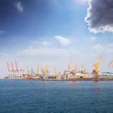 Bright red and blue cranes and colorful maritime containers stan. Bright red, blue and yellow cranes and colorful maritime containers stand in the dock at the Royalty Free Stock Photos