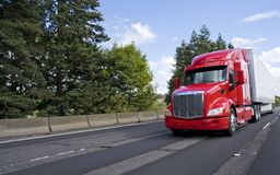 Bright modern long haul big rig semi truck with semi trailer moving on the green road. Bright red bonnet American modern long haul big rig semi truck with dry royalty free stock photo