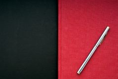 Bright red book on a black background. A stricking image of a silver pen on a bright red book on a black background stock photos