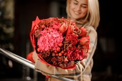 Bright red bouquet of flowers in woman hands royalty free stock image