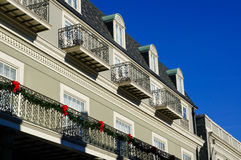 Bright Red Bows Along the Balcony. Bright red bows adorn a Christmas garland left up along the balcony of this building in New Orleans' French Quarter Royalty Free Stock Images