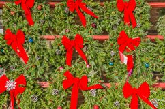 Bright Red Bows on Christmas Wreathes. Christmas wreathes with bright red bows, pine cones, ornaments, and berries Stock Image